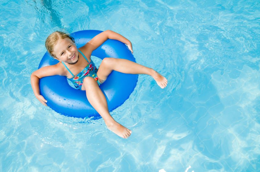 little girl in a float in a swimming pool